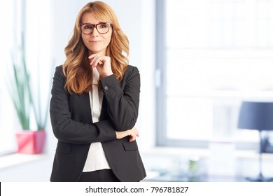 A well dressed happy businesswoman looking at the camera while standing at the office.