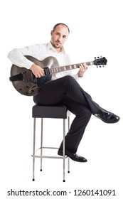 a well dressed jazz musician sitting on a stool and holding a guitar