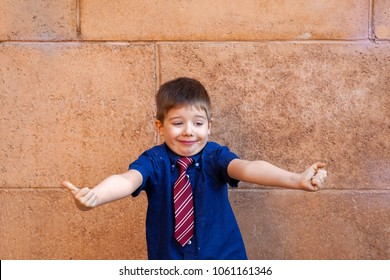 A well dressed, little boy wearing a tie, stands in front of a large block wall with his arms out and thumbs up in approval of the wedding cake he has all over his chin.  Funny expression, copy space.