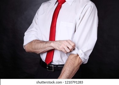 Well dressed man rolling up his sleeves