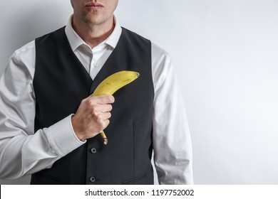Well dressed man in white shirt and black suit vest holding a banana like a gun. Concept of fake gangster / radical militant vegan. White background with copy space for text.