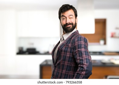 Well dressed man winking inside house