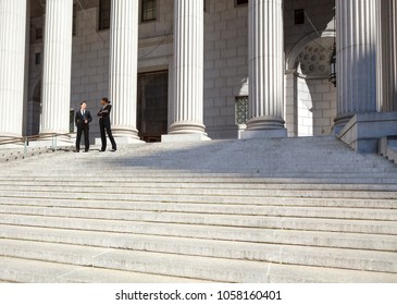 A well dressed man and woman converse on the steps of a legal or municipal building. Could be politicians, business or legal professionals.