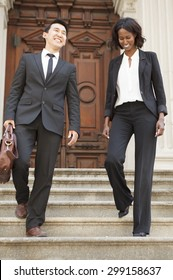 A well dressed man and woman laughing and walking down steps of a building. Could be business or legal professionals.