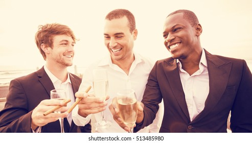 Well dressed men drinking champagne next to limousine on night out