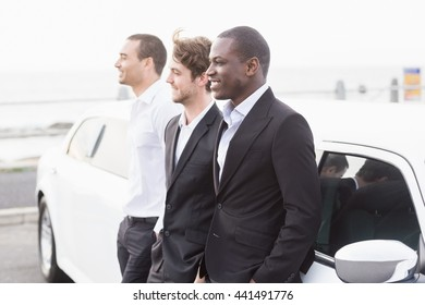 Well dressed men posing leaning on a limousine on a night out