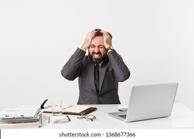 Well dressed office worker sitting at table grasping his head, nervous being in a difficult situation, has some work troubles, screams from panic gritting teeth,closed his eyes in despair hopelessness