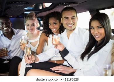 Well dressed people drinking champagne in a limousine on a night out