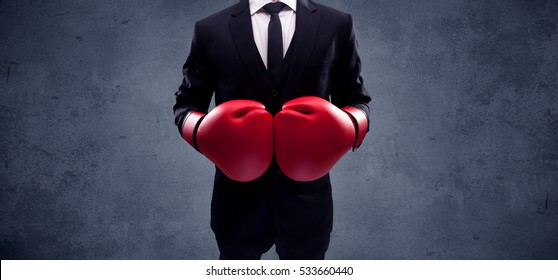 A well dressed sales person standing with red boxing gloves on his hand in front of urban grey wall background concept. - Shutterstock ID 533660440