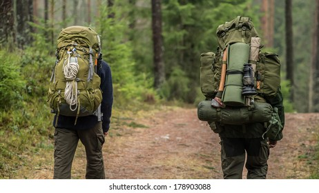 well equipped backpacking trekkers walking along a path in a swedish forest