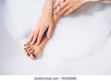 Well grooming woman's legs and hands in bath foam close up image