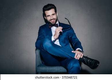 Well hello! Cheerful young handsome man in suit holding his sunglasses and looking at camera with smile while sitting on the chair against grey background