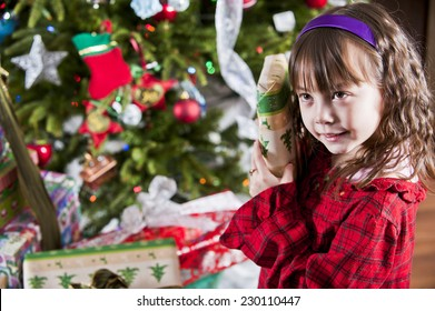 well hold on, what's this? / little girl checking a gift / to see what's inside