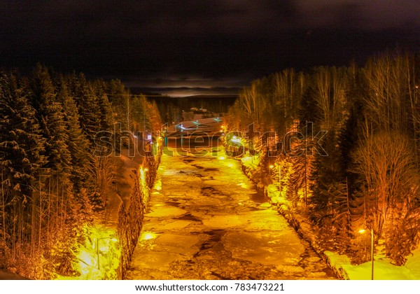 A well lit shipping canal in the winter just about to freeze over