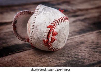 Well loved baseball splitting at the seams on a wooden background
