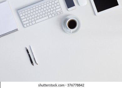 Well ordered clean working Place on White Desk with Business Electronics and every Day Life Items Pen Coffee Mug Computer Keyboard Telephone cropped Tablet Notepad