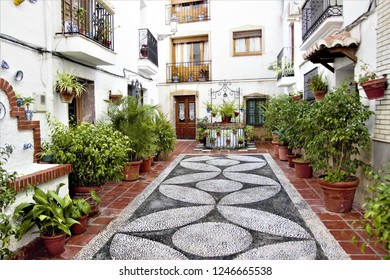 well and pots with flowers, typical corners of the Andalusian village of Salobreña, tourist destination, white village of Granada, in the Mediterranean sea, white villages, Spain, mosaic floor,