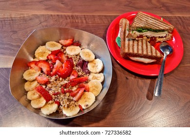 A well presented, healthy fruit and granola bowl with a panini