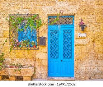 The well restored blue door and window behind bars of residential house in Naxxar town in Malta