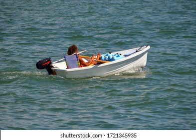 well tanned gay man leisurely cruising in a tiny white outboard engined powered dingy.