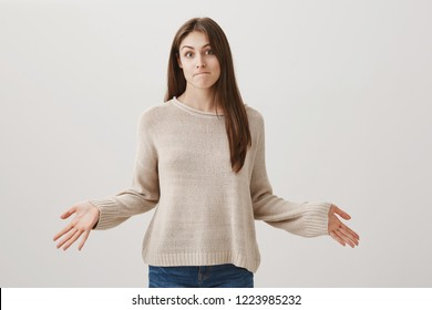 Well, that is how it is. Beautiful caucasian girl expressing blame and hiding truth, shrugging with spread hands and lips folded inside as if she has nothing to say or deal with issue, being clueless