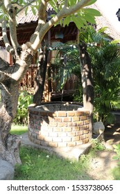 Well in tropical garden with brick paneling. Strong boat rope suspended on a pulley for pulling a pail with water. Wooden bungalow and tropical palm tree with lush green color in the background.