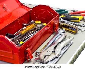 Well used old tools and red tool box on white background