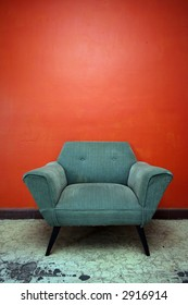 A well worn chair set against an orange wall in a room in Mexico.