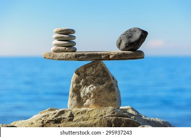 Well-balanced of pebbles on the top of sea boulder