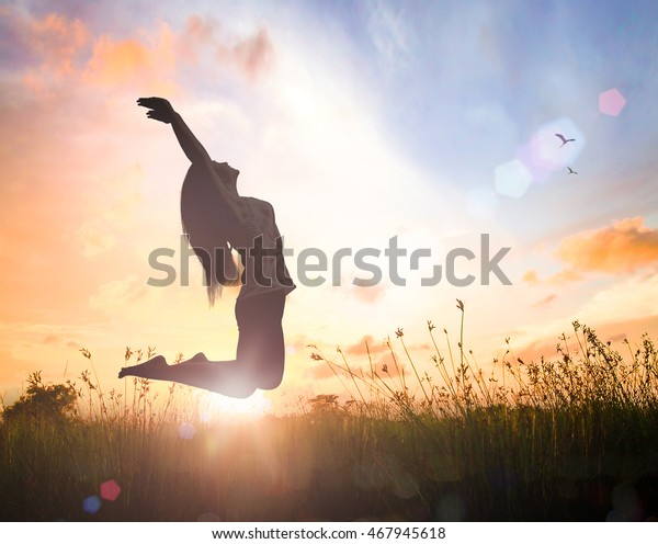 Wellbeing concept: Silhouette of happy woman jumping with her hands raised at orange autumn nature sunset background