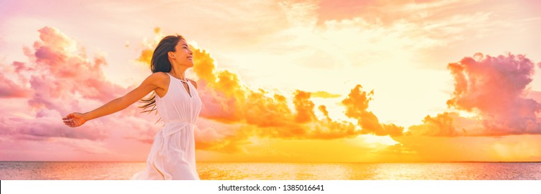 Wellbeing freedom happy woman jumping dancing of joy with open arms in the air blissful banner. Asian woman in sunset clouds pink sky background.