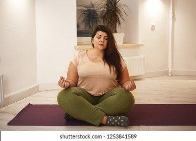 Wellbeing, harmony, yoga, meditation, zen and relaxation. Obese chubby young female sitting on mat, closing eyes and keeping legs crossed, meditating, searching for inner peace and balance