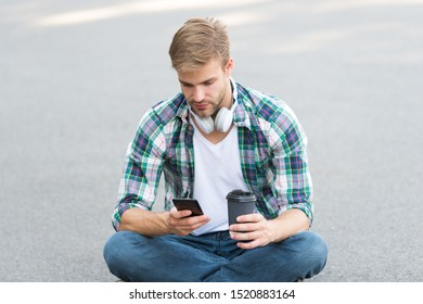 Wellbeing and health. Having coffee break. Man sit on ground while drinking coffee. Relax and recharge. Have fun during break. Guy carefree student enjoy coffee outdoors. College life. Life balance.