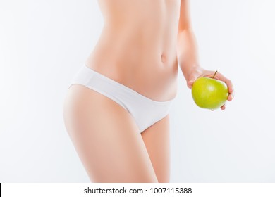 Wellbeing wellness intestine cosmetics concept. Cropped close up photo of skinny thin ideal perfect pure smooth woman's body hand showing green fresh apple near legs isolated on white background