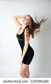 Well-built girl in tight, black skirt. Attractive female model throwing her hairs up in the air.