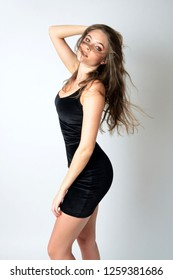 Well-built girl in tight, black skirt. Attractive female model with blond hairs.