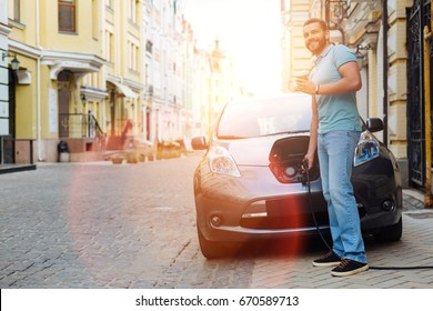 Well-built man charging e-vehicle and having coffee
