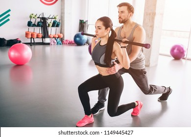 Well-built and strong trainer ih helping beautiful and slim girl to do some attacks carrying bodybar on her shoulders. They are doing this exercise very intensive but careful.
