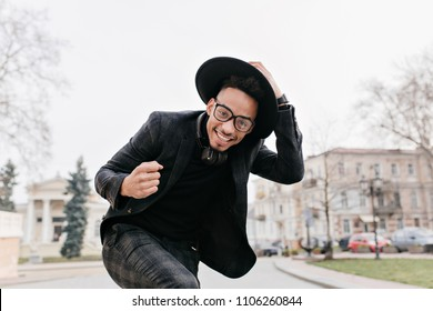 Well-dressed african man dancing in city square with smile. Laughing black guy touching his hat while posing outdoor under gray sky.