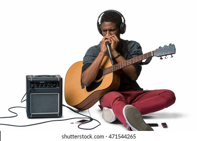 Well-dressed beatboxer with the acoustic guitar rehearses his new song. Nice guy sits on the floor near the amp and sings in the microphone.