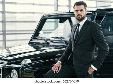Well-dressed customer choosing new premium car at a dealership showroom