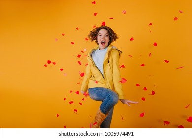 Well-dressed girl dancing, surrounded by red hearts. Indoor photo of gorgeous brunette female model celebrating valentine's day.