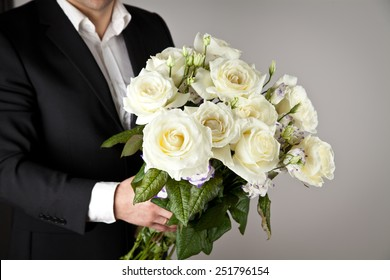 well-dressed man holding a bouquet of flowers, white roses. Holidays and celebrations. Wedding day.