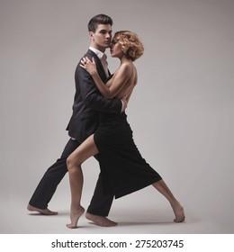 Well-dressed retro couple dancing tango over grey studio background
