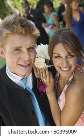 Well-dressed teenage couple standing outside school dance, elevated view