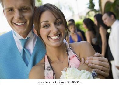 Well-dressed teenage couple standing outside school dance