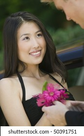 Well-dressed teenage girl receiving corsage from date