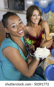 Well-dressed teenage girls drinking at school dance, elevated view