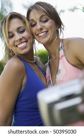 Well-dressed teenage girls taking picture outside school dance, low angle view