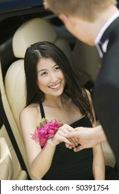 Well-dressed teenager girl being helped out of limo by date